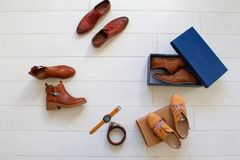 Flat lay set of unopened brown shoes and some brown accessories. Such as belt and watches. Top view Royalty Free Stock Photo