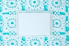 Flat, lay, a sheet of paper for text on a blue background with crocheted white vintage lace, winter theme, square ornament stock photo