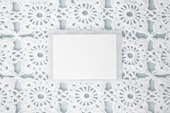 Flat, lay, a sheet of paper for text on a blue background with crocheted white vintage lace, winter theme, square ornament royalty free stock photography