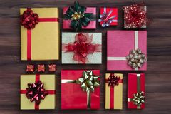 Flat lay shot of coloful boxes with colorful ribbon on wooden ba stock photo