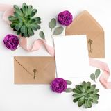 Flat lay shot of letter and eco paper envelope on white background. Wedding invitation cards or love letter with flowers. Valentine`s day or other holiday Royalty Free Stock Photos