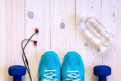 Flat lay shot of Sport equipment, shoes, water, earphone on wooden background. Flat lay shot of Sport equipment, shoes, water, earphone on wooden background Stock Photo