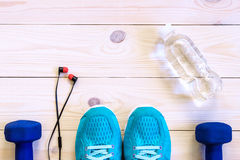 Flat lay shot of Sport equipment, shoes, water, earphone on wooden background. Stock Images