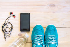 Flat lay shot of Sport equipment, shoes, water, earphone on wooden background.  Stock Photography