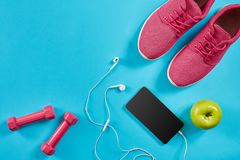 Flat lay shot of Sport equipment. Sneakers, dumbbells, earphones and phone on blue background. Sports and healthy lifestyle concept. Top view. Copy space stock photo