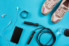Flat lay shot of Sport equipment. Sneakers, jump rope, earphones and phone on blue background. Sports and healthy lifestyle concept. Top view. Copy space stock image