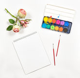 Flat lay sketchbook watercolor brushes paper rose flowers Stock Photos