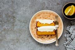 Lemon cake dessert. Flat lay of sliced lemon cake dessert with mascarpone cream in plate over grey concrete background top view - Image royalty free stock image