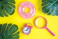 Flat lay of small swimming pool float toy with alarm clock and green leaves with magnifier isolated on yellow. Summertime concept. Tropical palm leaves and stock images