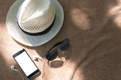 Flat lay of Smart Phoneใ. Flat lay of Smart Phone with earphones, sunglasses and a white hat on the brown towel background. With copy space, dicut of phone`s Stock Images