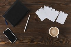 Flat lay with smartphone, notebook, pencil and cup of coffee. On wooden tabletop Stock Photos