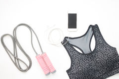Flat lay of smartphone, sport bra and sport equipments on white. Background, Workout and Fitness concept Stock Image