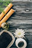 Flat lay with spa and massage treatment arrangement with towel, essential oil, pebbles and chrysanthemum flower. On wooden tabletop royalty free stock photography