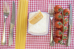 Flat lay of spaghett icherry tomatoes and parmesan between cutle Stock Photos