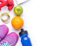 Flat lay of Sport equipment. Sneakers, dumbbells, water, towel, fruits and phone on white background. View from above.  Royalty Free Stock Images