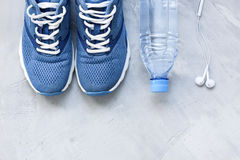 Flat lay sport shoes, bottle of water and earphones on gray conc Stock Photography