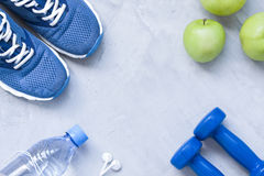Flat lay sport shoes, dumbbells, earphones, apples, bottle of wa. Ter on gray concrete background. Concept healthy lifestyle, sport and diet. Selective focus Royalty Free Stock Images