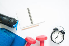 Flat lay of sport yoga equipments, notebook and clock on white Royalty Free Stock Photos