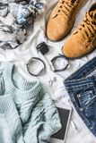 Flat lay spring women`s clothing set - suede boots, sweater, jeans, scarf, accessories on light background. Top view royalty free stock photo