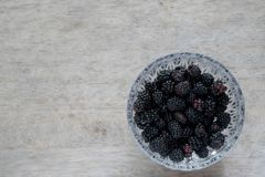 Ripe blackberries in crystal bowl on table Stock Images