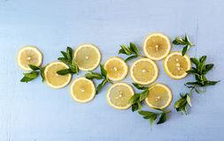 Flat lay still life with mint and lemon on blue background. Pop Stock Images