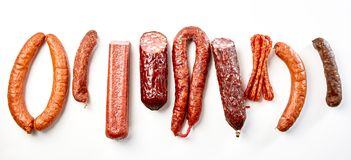 Flat lay still life of a mix of spicy sausages. Flat lay still life of a selection of spicy dried or smoked beef and pork sausages isolated on white in a royalty free stock image