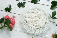 Flat lay still life with roses. Marshmallows and a rose on a white wooden background.flat lay Royalty Free Stock Images