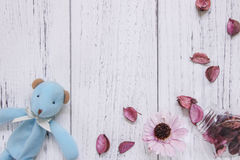 Flat lay stock photography vintage white painted wood floor purp. Le flower petals and glass bottle blue bear doll Royalty Free Stock Photos