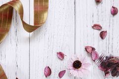 Flat lay stock photography vintage white painted wood floor purp. Le flower petals and glass bottle golden ribbon Royalty Free Stock Images