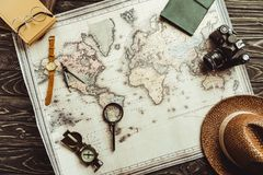 Flat lay with straw hat, map, magnifying glass, compass and retro photo camera on dark. Wooden tabletop royalty free stock photo