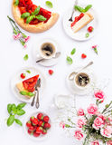 Flat lay with strawberry cheesecake. Flat lay with coffee, delicious homemade strawberry cheesecake and flowers over white. Top view stock photos