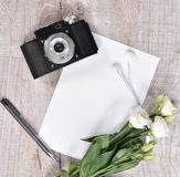Flat lay style with camera, roses, notebook, earphones and pen Royalty Free Stock Photography