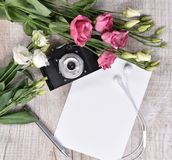Flat lay style with camera, roses, notebook, earphones and pen Stock Images