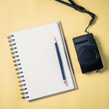 Flat lay style of empty book and pencil and retro camera. With yellow pastel background and copy space for design work concept travel Royalty Free Stock Photography