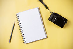 Flat lay style of empty book and pencil and retro camera. With yellow pastel background and copy space for design work concept travel Royalty Free Stock Photo
