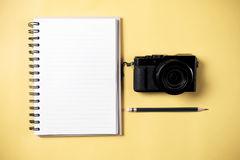 Flat lay style of empty book and pencil and retro camera. With yellow pastel background and copy space for design work concept travel Royalty Free Stock Image