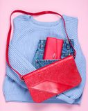 Flat lay style fashion clothes. On pink background. Women's sweater, jeans, retro bag, red wallet. Top view. Fashion look stock photo
