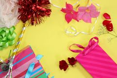 Flat lay style girl`s birthday concept. A flat lay style concept of a girl`s birthday party theme, with pink flowers, gift bags and ribbons laid out on bright royalty free stock photos