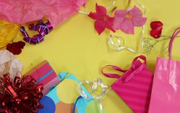 Flat lay style girl`s birthday concept. A flat lay style concept of a girl`s birthday party theme, with pink flowers, gift bags and ribbons laid out on bright stock photo