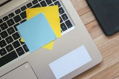 Flat lay style image of modern laptop computer keyboard. Yellow and blue sticky note to the computer. On a brown wooden desk stock photo