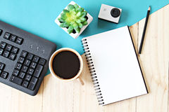 Flat lay style of office workspace desk with blank notebook paper, computer keyboard, cup of coffee and action camera Stock Photo