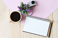 Flat lay style of office workspace desk with blank notebook paper, cup of coffee Stock Photography