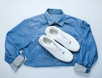 Flat lay style. White hipster sneakers with denim shirt on gray background. Retro culture, top view royalty free stock images