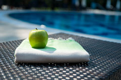 A flat lay summer accessories close-up of a white and green Turkish peshtemal / towel and green apple on a rattan lounger. royalty free stock image