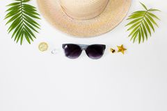 Flat lay summer beach holiday accessories on white background with palm leaf, straw hat and and sunglasses. Space for text. Travel and beach vacation, top view royalty free stock image