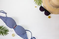 Flat lay summer beach holiday accessories on white background with palm leaf, straw hat and and sunglasses. Space for text. Travel and beach vacation, top view royalty free stock images