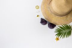 Flat lay summer beach holiday accessories on white background with palm leaf, straw hat and and sunglasses. Space for text. Travel and beach vacation, top view stock photography