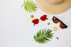 Flat lay summer beach holiday accessories on white background with palm leaf, straw hat and and sunglasses. Space for text. Travel and beach vacation, top view stock photo