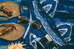 Flat lay of summer fashion with blue bikini swimsuit, camera and other girl accessories on blue wooden  background.  Stock Images