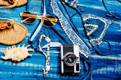 Flat lay of summer fashion with blue bikini swimsuit camera and other girl accessories on blue wooden background.  Stock Image